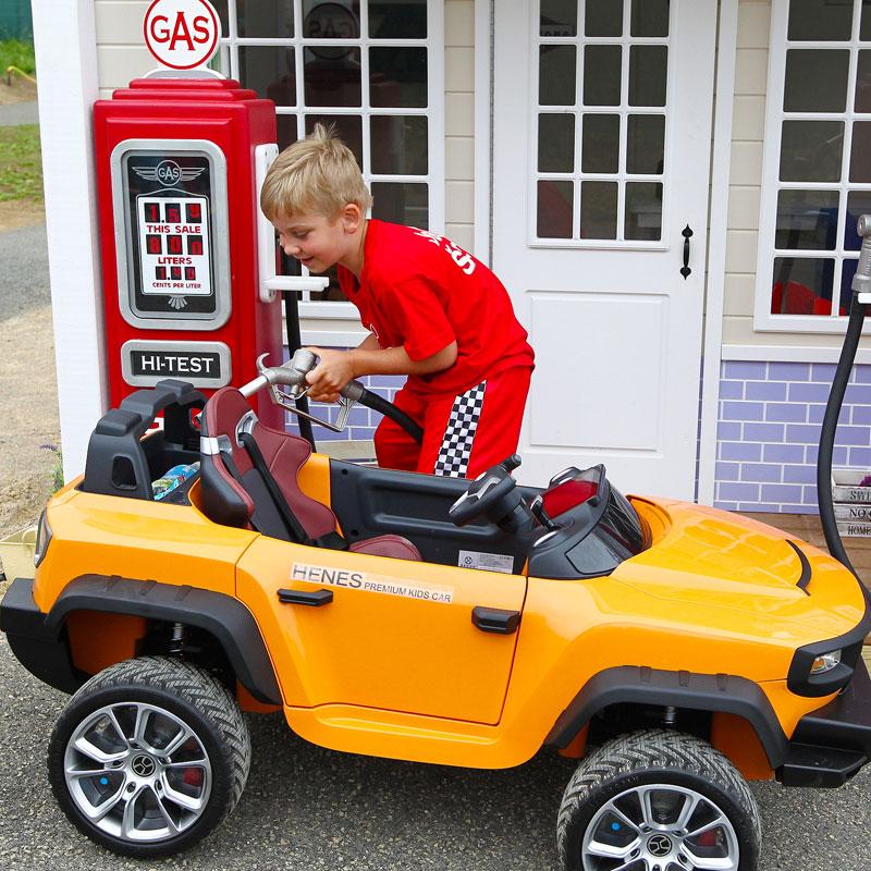 Malý chlapec so svetlými vlasmi, tankuje detské autíčko na detskej čerpacej stanici