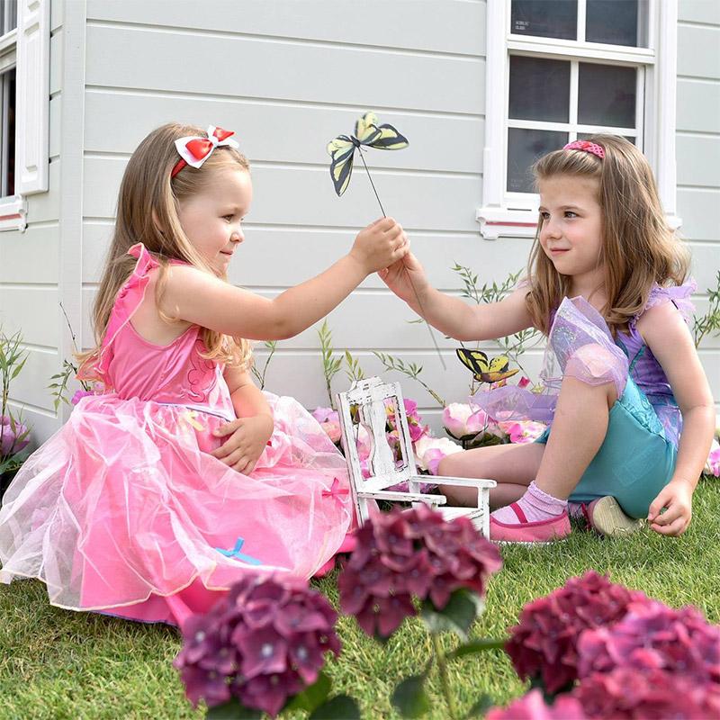 malé dievčatká v kostýmoch princezien sa hrajú pri domčeku v záhradke