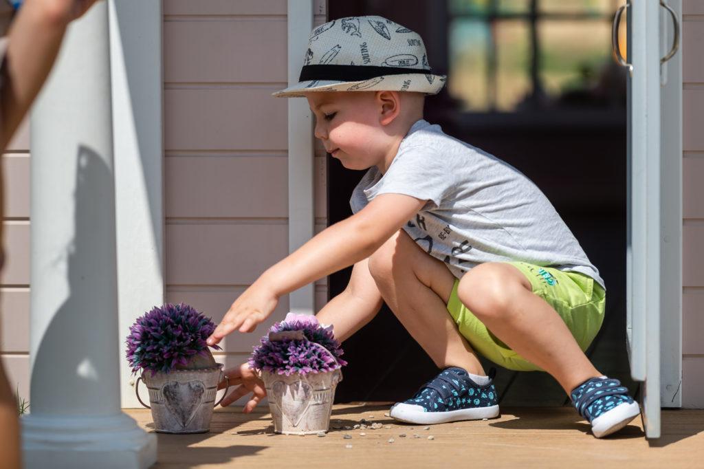 chlapček upravuje kvetinky na terase detského domčeka v Donovalkove